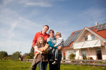 Happy,Family,Standing,In,Front,Of,House,With,Solar,Panels